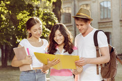 Friends studying books on the move before exams. Three friends studying books on the move before exams Royalty Free Stock Photos