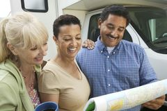 Friends studying road map beside motor home Stock Photos