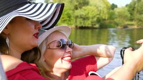 Friends in stylish outfits taking selfie photo during water trip. Smiling female friends in stylish outfits relaxing on sailing boat and taking selfie photo on stock footage