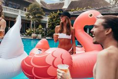 Friends at summer pool party. Friends in a swimming pool having beers. Woman in bikini sitting on a inflatable toy and having beer with friends at summer pool stock photography