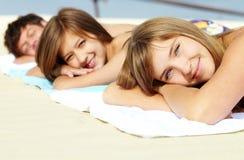 Friends sunbathing. Portrait of three teenage friends lying on the beach and sunbathing Royalty Free Stock Photography