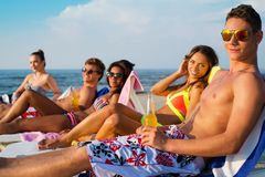 Friends sunbathing on a beach Stock Images