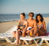 Friends sunbathing on a beach Stock Photography