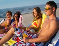 Friends sunbathing on a beach Royalty Free Stock Photography