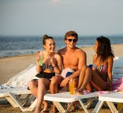 Friends sunbathing on a deck chairs on a beach Royalty Free Stock Photos