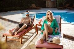 Friends sunbathing, lying on chaises near swimming pool. Young friends sunbathing, lying on chaises near swimming pool. Copy space royalty free stock photo