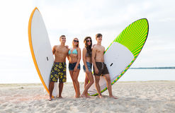 Friends in sunglasses with surfboards on beach Royalty Free Stock Photography