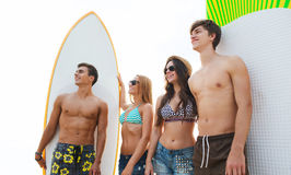Friends in sunglasses with surfboards on beach. Friendship, sea, summer vacation, water sport and people concept - group of smiling friends wearing swimwear and stock image