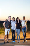 Friends at sunset vertical. Friends standing together and smiling with sunset and plenty of copy space Stock Image