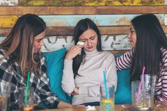 Girls friends supporting and consoling crying young woman at restaurant stock photography