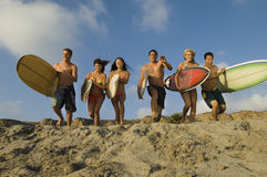 Friends With Surfboards Running On Sandy Beach. Group of multiethnic friends with surfboards running on sandy beach Royalty Free Stock Photo