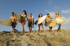 Friends With Surfboards Running On Sandy Beach. Group of multiethnic friends with surfboards running on sandy beach Stock Photo