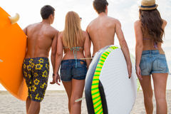 Friends with surfboards on summer beach. Friendship, sea, summer vacation, water sport and people concept - group of friends wearing swimwear with surfboards on stock image