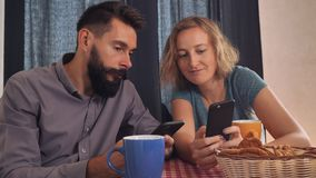 Friends surfing internet on cellular. Young happy couple using gadgets at home. Smiling girl holding smartphone showing boyfriend some funny picture. Boyfriend stock footage