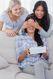 Friends surprising brunette with a gift Royalty Free Stock Photography