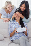 Friends surprising brunette woman with a gift Royalty Free Stock Photography