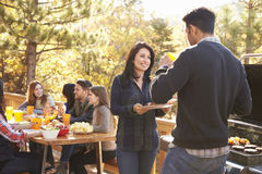 Friends at a table and two talking by grill at a barbecue Stock Images