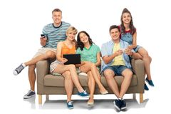 Friends with tablet pc and smartphones sit on sofa Stock Photography