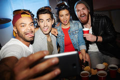 Friends Taking Crazy Selfie at Awesome Night Club Party. Group of modern young people chilling at night club party, posing for selfie photo, grimacing and having Royalty Free Stock Photos