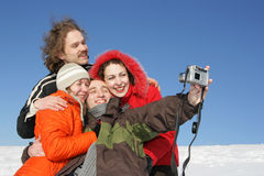 Friends taking a photo. Four friends taking a photo in winter Royalty Free Stock Photos