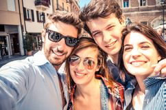 Friends taking photo of themselves. Group of friends taking a selfie - Students smiling at camera and having fun outdoors in a sunny day - Students enjoying the stock image