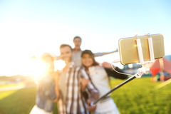 Friends taking a photos against grass and blue sky stock photography