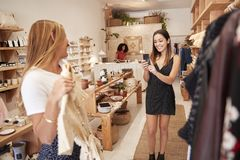 Free Friends Taking Photos On Mobile Phone As They Choose Dresses In Independent Fashion Store Royalty Free Stock Photo - 144599155