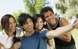 Friends Taking Self Portrait With Digital Camera At Park Royalty Free Stock Photos