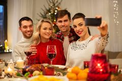 Friends taking selfie at christmas dinner royalty free stock images