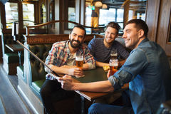 Friends taking selfie and drinking beer at bar Royalty Free Stock Photos