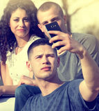 Friends taking selfie. Group of young people having fun taking selfie with smarthphone in park Stock Photos