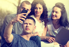 Friends taking selfie. Group of young people having fun taking selfie with smartphone in park Stock Photography