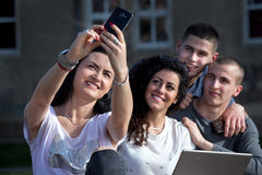 Friends taking selfie. Group of young students having fun taking selfie with smarthphone in front of university Royalty Free Stock Photos