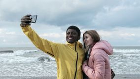 Friends taking selfie at phone at the beach. Two multicultural persons of black guy and caucasian female make a photography at smart phone close up. Positive fun stock video footage