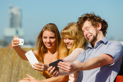 Friends taking selfie photo with smartphone. Stock Photography