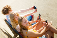 Friends taking selfie photo with smartphone. Stock Images