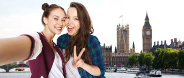 Friends taking selfie and showing peace in london. People, travel, tourism and friendship concept - happy smiling pretty teenage girls taking selfie and showing Stock Photo