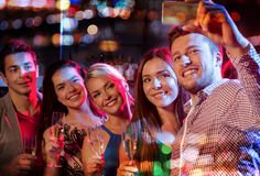 Friends taking selfie by smartphone in night club Stock Photography