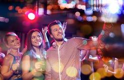 Friends taking selfie by smartphone in night club Stock Photo
