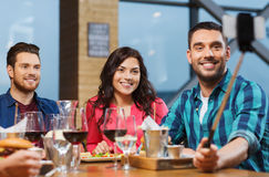 Friends taking selfie by smartphone at restaurant Royalty Free Stock Photo