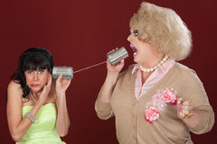 Friends Talk Through Cans. Woman with friend in drag talk through tin cans Royalty Free Stock Photo