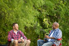 Friends talking and camping. Royalty Free Stock Images
