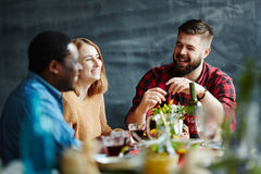 Friends talking at dinner. Three friends having dinner together and laughing Royalty Free Stock Images
