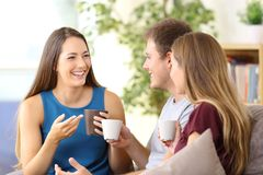 Friends talking and drinking coffee at home. Three happy friends talking and drinking coffee sitting on a couch at home Stock Photo