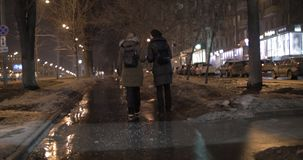 Friends talking during evening walk in winter city stock video footage