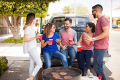 Friends talking about football in a barbecue. Group of five attractive friends talking about a football game over drinks during a hamburger barbecue stock image