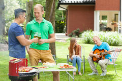 Friends talking on a garden party Royalty Free Stock Image