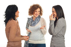 Friends talking and laughing. Happy three friends women having conversation and laughing together isolated on white background Stock Photos