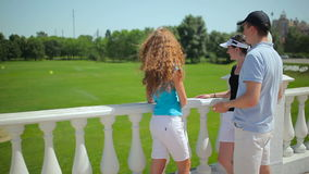 Friends are talking and laughing near the course. Three friends are talking and laughing. Two women and man are standing near the course. The people are smiling stock footage