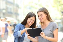 Friends talking about online content in a tablet. Two happy friends talking about online content in a tablet in the street Stock Photos